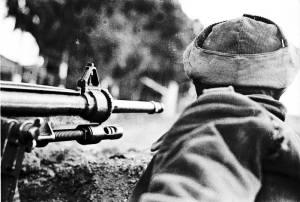 Soldado republicano vuelto de espaldas junto al cañon de una ametralladora. Archivo Histórico del Partido Comunista de España.