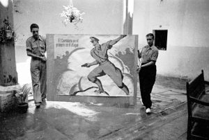 Dos miembros del comisariado de propaganda transportan un cartel.